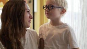 La mujer joven hermosa y su hijo están charlando almacen de video