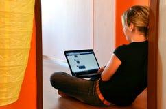 La mujer joven hojea su página del facebook en el ordenador portátil asentado en el piso imagenes de archivo