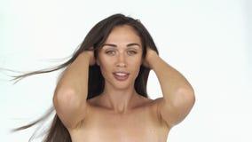 La mujer joven imponente con las pecas y los hombros desnudos presenta para una cámara que sacude su pelo largo atractivo almacen de metraje de vídeo