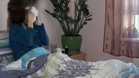 La mujer joven infeliz enferma de la gripe miente en cama Doctor de llamada de sexo femenino metrajes