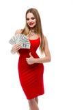 La mujer joven insano hermosa en el vestido rojo que lleva a cabo muchos 100 billetes de dólar y que muestra manosea con los dedo Foto de archivo libre de regalías