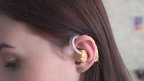 La mujer joven inserta un audífono en su cierre del oído para arriba almacen de video