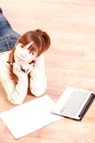La mujer joven japonesa con el ordenador portátil piensa en algo Foto de archivo