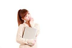 La mujer joven japonesa con el ordenador portátil piensa en algo Imágenes de archivo libres de regalías