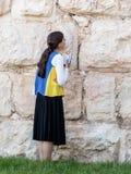 La mujer joven judía religiosa lee el libro con rezos fuera de las paredes de la fortaleza de la ciudad vieja de Jerusalén, Israe Fotos de archivo