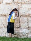 La mujer joven judía religiosa lee el libro con rezos fuera de las paredes de la fortaleza de la ciudad vieja de Jerusalén, Israe Foto de archivo libre de regalías