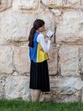 La mujer joven judía religiosa lee el libro con rezos fuera de las paredes de la fortaleza de la ciudad vieja de Jerusalén, Israe Imagen de archivo