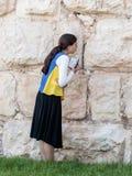 La mujer joven judía religiosa lee el libro con rezos fuera de las paredes de la fortaleza de la ciudad vieja de Jerusalén, Israe Imágenes de archivo libres de regalías
