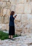 La mujer joven judía religiosa lee el libro con rezos fuera de las paredes de la fortaleza de la ciudad vieja de Jerusalén, Israe Fotos de archivo libres de regalías