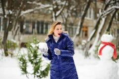 La mujer joven juega bolas de nieve Fotografía de archivo