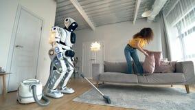 La mujer joven juega con las almohadas mientras que el robot blanco hace la limpieza del vacío almacen de metraje de vídeo