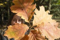 La mujer joven juega con las ramas con las hojas de otoño Fotos de archivo