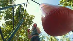 La mujer joven juguetona en ropa de deportes bate un saco de arena, entrenamiento en el parque del verano, a cámara lenta almacen de metraje de vídeo