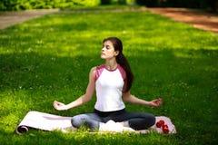 La mujer joven juguetona que se relaja en la sol, haciendo yoga ejercita Imagenes de archivo