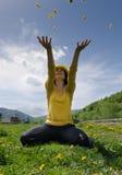 La mujer joven lanza las flores amarillas en el aire Foto de archivo