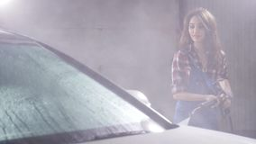 La mujer joven lava el coche con la lavadora de alta presión metrajes