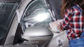 La mujer joven lava el coche con una esponja metrajes