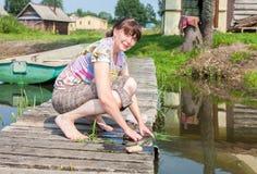 La mujer joven lava la ropa en el embarcadero de madera por el lago en verano Fotografía de archivo libre de regalías