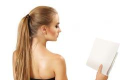 La mujer joven lee el periódico Imagen de archivo