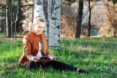 La mujer joven lee la revista en el parque Foto de archivo