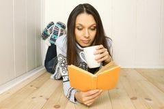 La mujer joven lee un libro Fotos de archivo libres de regalías