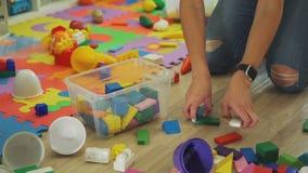 La mujer joven limpia el cuarto de niños de los juguetes metrajes