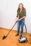 La mujer joven limpia el piso con el aspirador Fotos de archivo libres de regalías