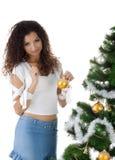 La mujer joven linda adorna el árbol de navidad Imagenes de archivo