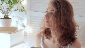 La mujer joven linda bebe el café de una taza con las melcochas almacen de metraje de vídeo