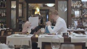 La mujer joven linda del retrato se sienta con los papeles en la tabla en restaurante con un hombre barbudo confiado que la muest metrajes