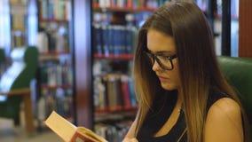 La mujer joven lista se sienta en la butaca y lee el libro en la biblioteca almacen de metraje de vídeo