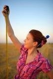 La mujer joven lleva a cabo la ruleta del tapeline en las manos en el campo Imagen de archivo libre de regalías