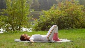 La mujer joven lleva a hombros ejercicio de la mosca mientras que miente en una estera de la yoga en una orilla del río metrajes