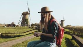 La mujer joven local se sienta cerca de molino rústico viejo La vaquera en sombrero con el pelo largo y la mochila roja hace un r almacen de video