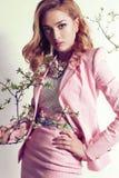 La mujer joven magnífica con el pelo rizado rubio lleva el traje y la joya elegantes Imagenes de archivo