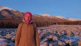 La mujer joven medita en el pie de las montañas almacen de metraje de vídeo