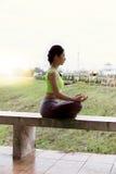 la mujer joven medita mientras que practica la yoga al aire libre en parque, con referencia a Foto de archivo