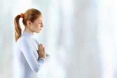 La mujer joven meditate sobre la cascada imagen de archivo