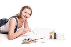 La mujer joven miente feliz en el dibujo del piso adentro Fotos de archivo
