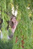 La mujer joven mira debido a ramas del sauce Fotografía de archivo