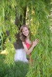 La mujer joven mira debido a ramas del sauce Fotos de archivo libres de regalías