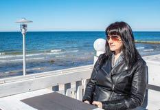 La mujer joven mira el mar que se sienta en el café al aire libre fotos de archivo