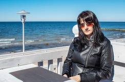 La mujer joven mira el mar que se sienta en el caf? al aire libre imagenes de archivo