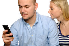 La mujer joven mira el teléfono de su marido. Fotografía de archivo