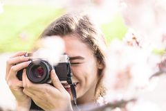 La mujer joven mira en la lente y risas de cámara foto de archivo libre de regalías