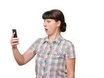 La mujer joven mira fijamente la pantalla del teléfono Fotos de archivo libres de regalías