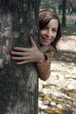 La mujer joven mira hacia fuera de detrás un árbol Fotografía de archivo