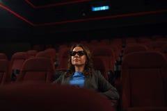 La mujer joven mira la película 3D en el cine y bebe el café, lo Foto de archivo