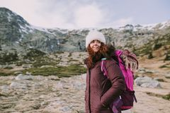 La mujer joven mira lejos mientras que goza de la montaña fotografía de archivo