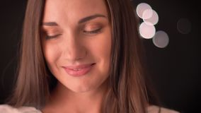 La mujer joven mira lejos tímido y las sonrisas en un fondo de las blured-luces almacen de metraje de vídeo